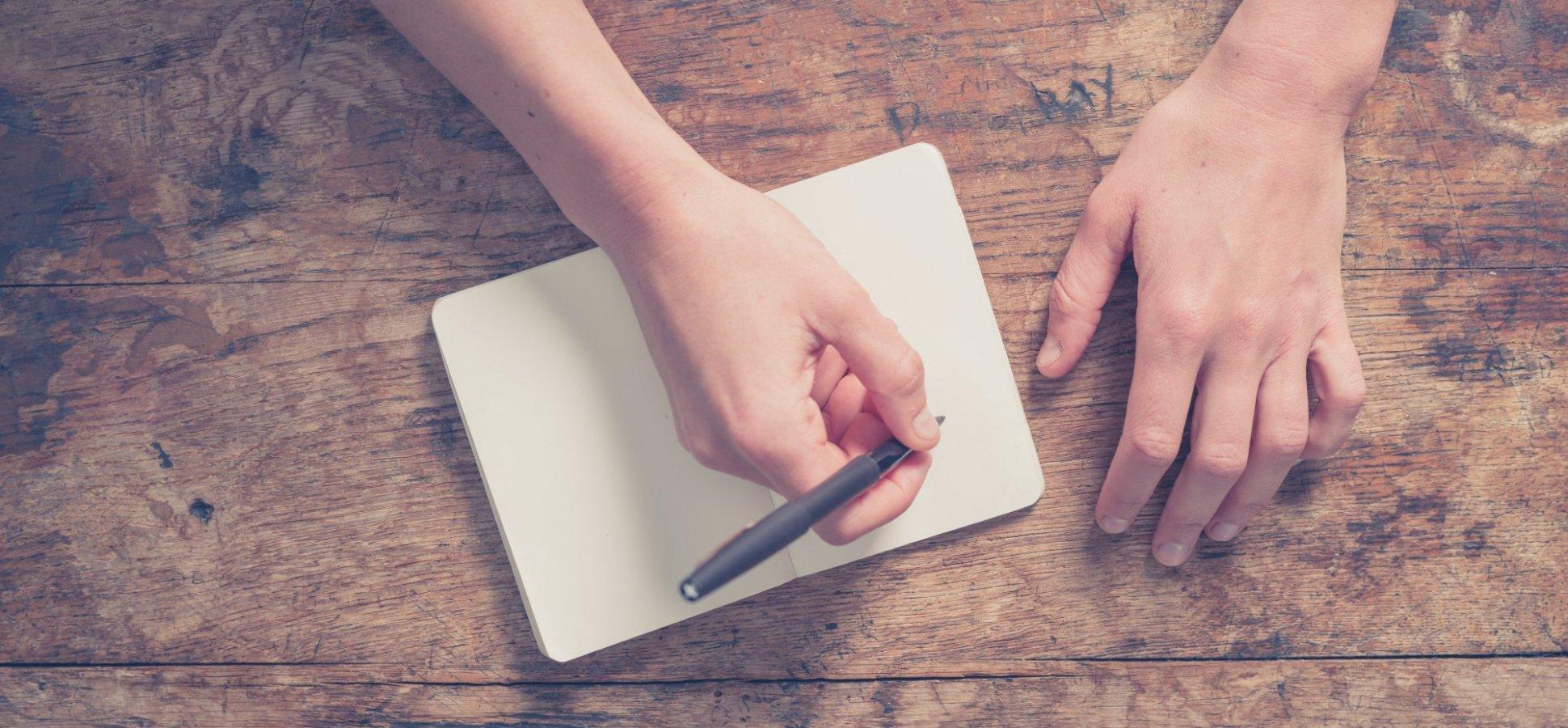 Na imagem, uma pessoa segura uma caneta em cima de um livro.