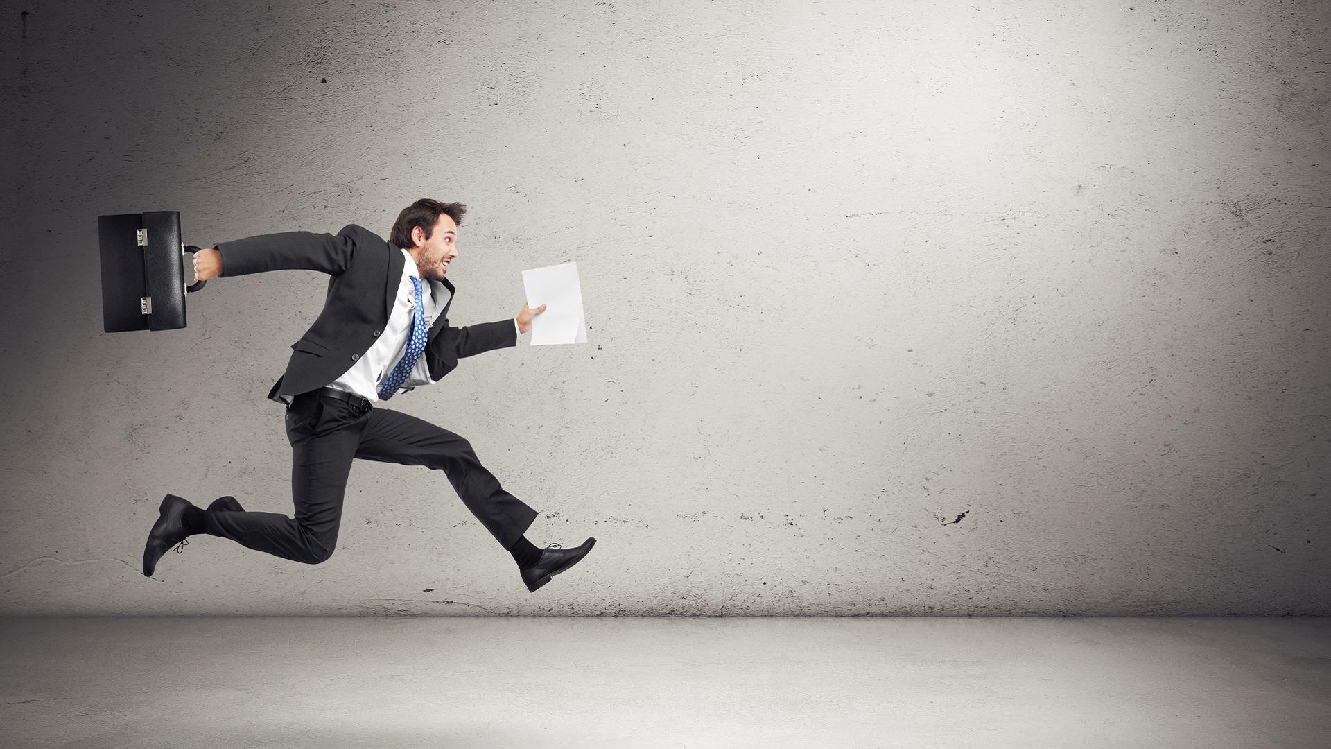 Na imagem há um homem vestido de terno, com uma maleta e papel em mãos, correndo como se estivesse participando de uma corrida com obstáculos.
