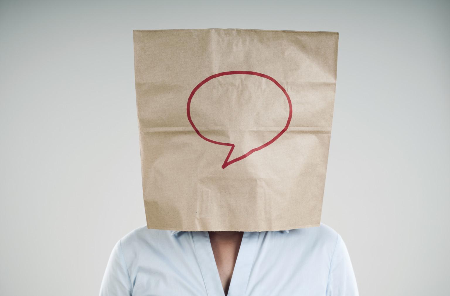 Na imagem, uma pessoa está com um saco de papel no rosto, com o desenho de um balão de fala, para ilustrar o que é awareness.