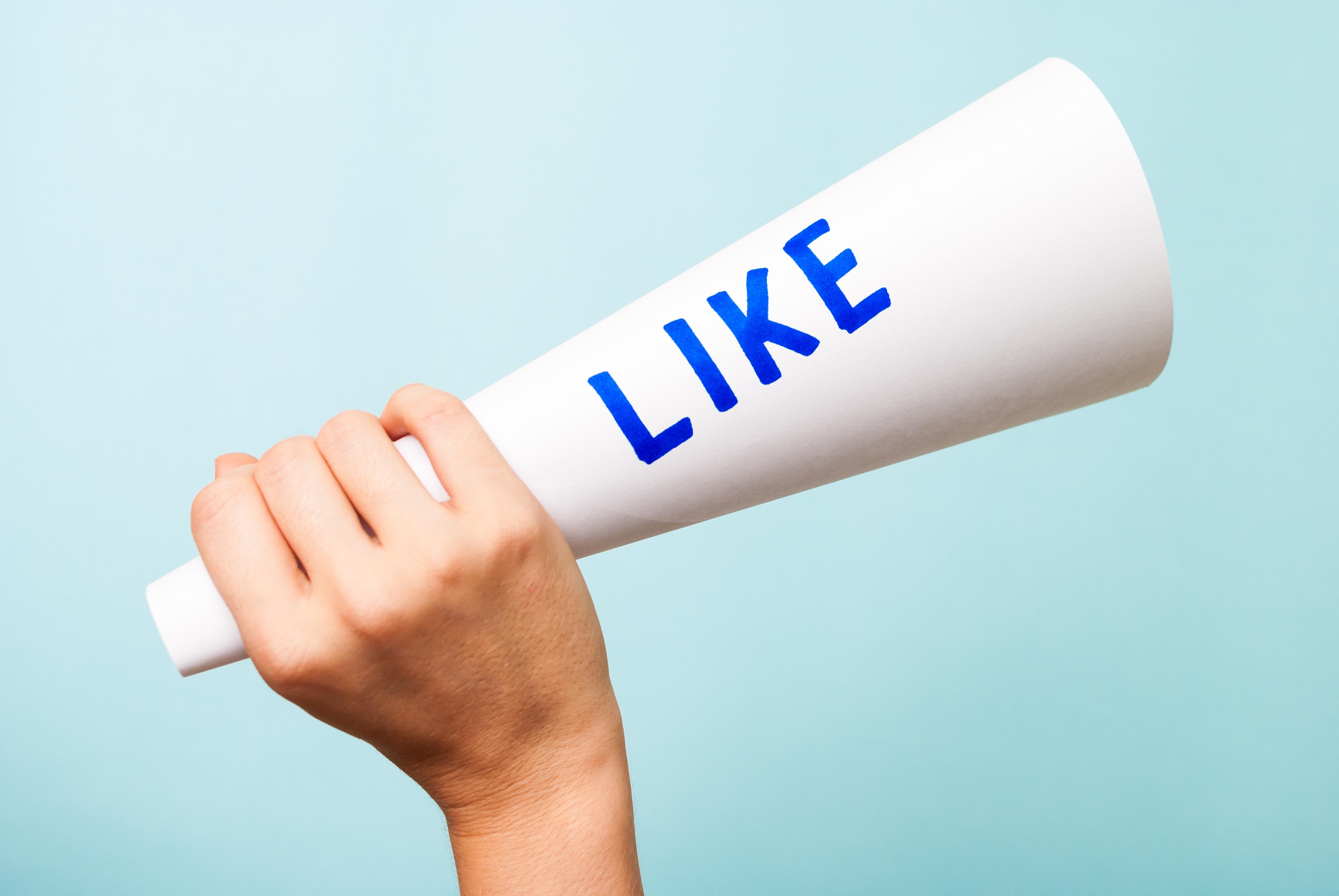 Na imagem, uma mão segura um cone escrito Like, ilustrando o envolvimento entre público e marca