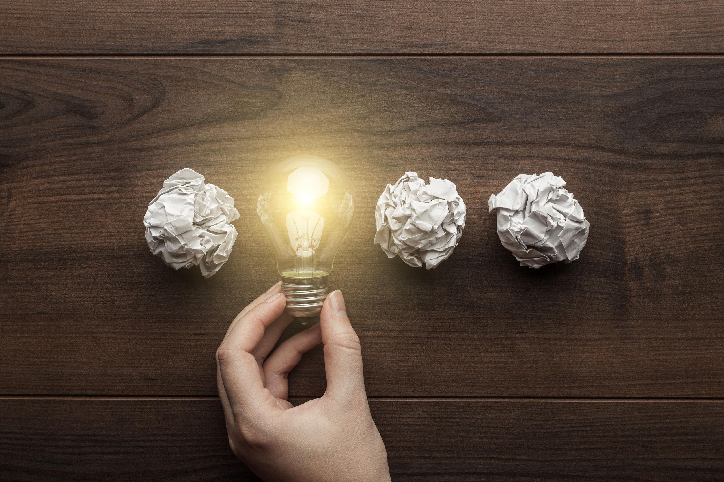 Na imagem, três bolas de papel amassado com uma lâmpada acesa, ilustrando a ideia que parte das três dicas de marketing de conteúdo