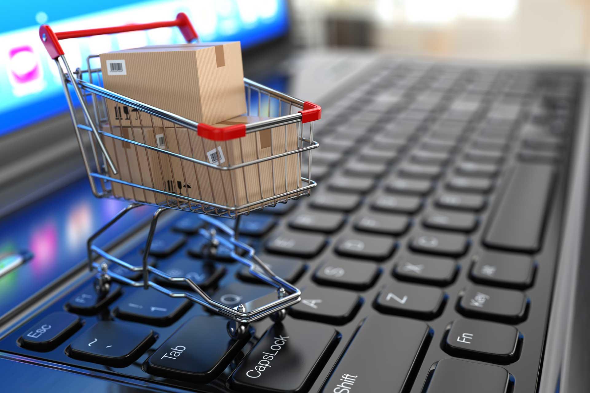 Na imagem, um carrinho de compras cheio pequeno se encontra em cima de um teclado de notebook, ilustrando o inbound commerce