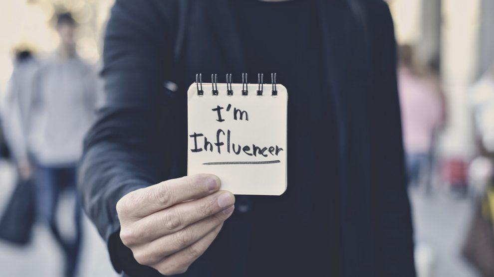 """Na imagem, uma pessoa segura um recado em um papal escrito """"sou influenciador""""."""